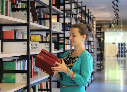 Picture of Woman with books  in a library.